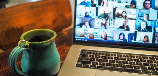 mug next to laptop hosting a virtual meeting