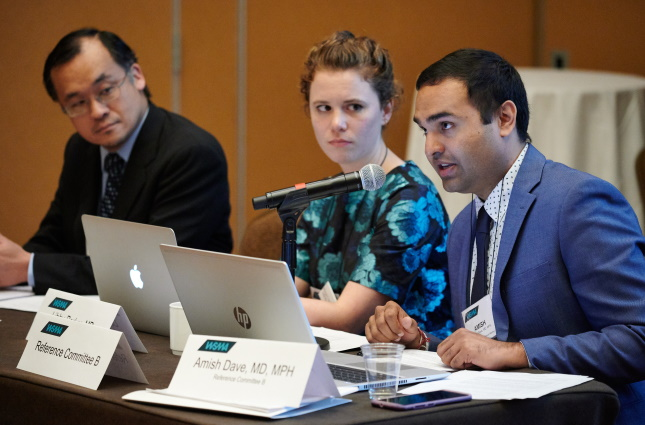 physicians sitting at a table, speaking into microphones